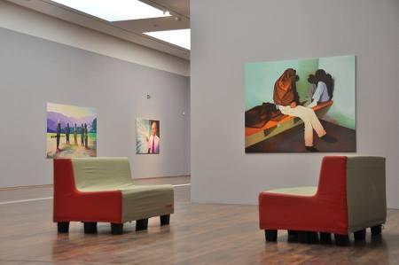 Az előtérben: <em>Két fiatal festő vizsgálati fogságban,</em> 2011, olaj, vászon, 140 × 170 cm, Museum Angerlehner, Wels, Ausztria; A háttérben: <em>Egy sík szférikus átalakulása,</em> olaj, vászon, 150 × 240cm, Perneczky Gyűjtemény, Bécs, Ausztria; <em>A barikád elzárja az utcát, de megnyitja az utat / Egy német Londonban,</em> 2010, olaj, vászon, 120 × 170cm, Fotó: Árokszállási Ronald