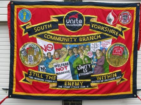 Ed Hall: a UNITE szakszervezet transzparense a társadalombiztosítási rendszer védelmében rendezett felvonuláson Manchesterben 2013. szeptember 29-én © V&A