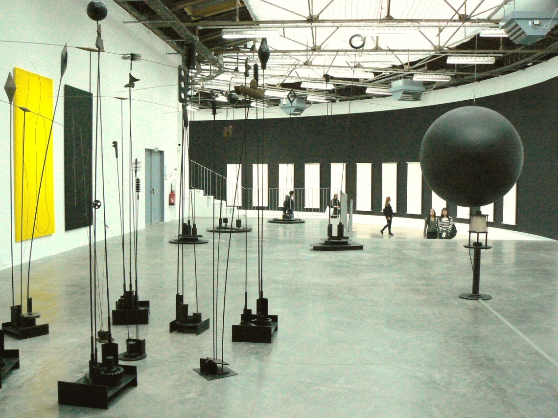 Az előtérben a Signal à Quatre Bras (1967, fém, 320 × 320 × 49 cm, Laffanour Galerie Downtown, Párizs), továbbá a Signal Lumineux (1976, fém, elektronika, 240 cm, Laffanour Galerie Downtown, Párizs), a háttérben a 6 Musicales (2000–2003, festett fa, áramkör, kábel, fém, 257 × 100 cm, Takis Foundation, Athén).