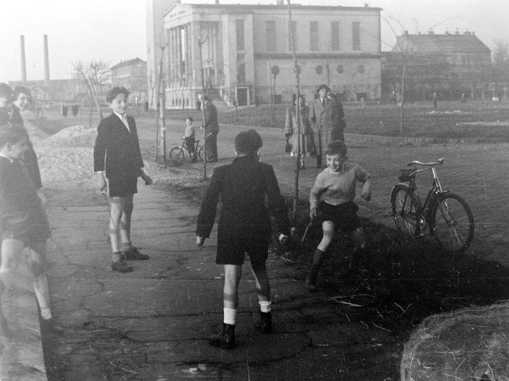 Fekete-fehér kép a rakparton ágakkal kardozó gyerekekről.